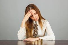 La donna considera le pile di monete di oro Immagine Stock