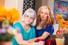 La donna consola l'amico in cucina brillantemente colorata immagini stock