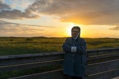 La donna contiene il momento momentaneo del tramonto immagine stock libera da diritti