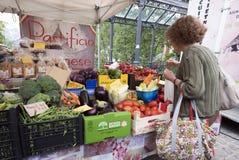 La donna controlla le verdure sul mercato dell'aria aperta di briancon nell'Alta Provenza francese Fotografie Stock Libere da Diritti