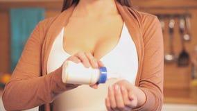 La donna controlla la temperatura del latte La madre preoccupantesi controlla la temperatura di latte da una bottiglia fotografia stock