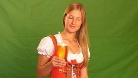 La donna in costume bavarese ride e mostra i pollici su Schermo verde video d archivio