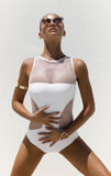 La donna in costume da bagno bianco ed occhiali da sole dorati con capelli su posa su fondo Colpo di alta moda fotografie stock
