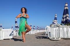 La donna in costume da bagno e in pareo si leva in piedi sulla spiaggia immagini stock