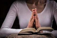 La donna cristiana graziosa sta leggendo un libro religioso fotografie stock libere da diritti