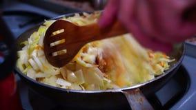 La donna cucina il cavolo e le carote brasati nella pentola archivi video