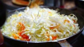 La donna cucina il cavolo e le carote brasati nella pentola video d archivio