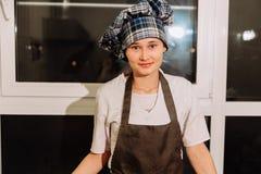 La donna cuoce le torte I confettieri producono i dessert Produrre i panini Pasta sulla tavola immagini stock