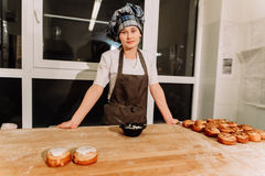 La donna cuoce le torte I confettieri producono i dessert Produrre i panini Pasta sulla tavola immagine stock libera da diritti