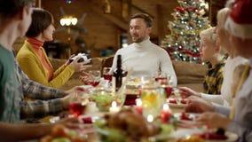 La donna dà il regalo di natale per equipaggiare durante la cena di festa degli amici stock footage