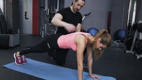 La donna d'aiuto dell'istruttore fa un esercizio della plancia stock footage