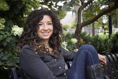 La donna dai capelli abbastanza riccia sorride nella macchina fotografica Immagini Stock Libere da Diritti