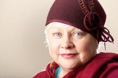 La donna dai capelli bianchi nel rosso ha messo le piume al cappello ed allo scialle Fotografia Stock