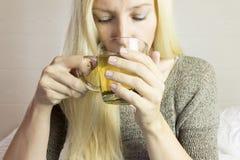 La donna dai capelli lunghi bionda beve il tè verde caldo in tazza trasparente immagini stock