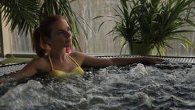 La donna dai capelli rossi in costume da bagno giallo si rilassa in acque di ribollimento della Jacuzzi stock footage
