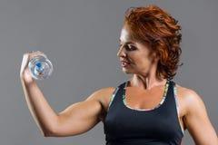 La donna dai capelli rossi di forma fisica atletica adulta negli sport uniforma con una bottiglia dell'acqua Fotografia Stock
