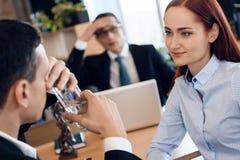 La donna dai capelli rossi sveglia esamina l'uomo, bicchiere dell'acqua nell'ufficio del ` s dell'avvocato per il divorzio immagine stock