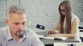 La donna dalla vista posteriore sta chiacchierando con l'uomo all'ufficio facendo uso dello smartphone video d archivio