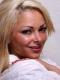 La donna dei capelli biondi sta esaminando la sua spalla Fotografia Stock