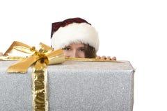 La donna del Babbo Natale sta nascondendosi dietro il regalo di natale Immagine Stock