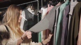 La donna del cliente sta scegliendo un indumento in un negozio in un centro commerciale archivi video