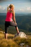 La donna del corridore riposa su una cima della montagna dopo l'allenamento corrente Immagine Stock