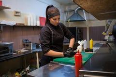 La donna del cuoco prepara la cucina del ristorante di sushi dell'alimento Immagine Stock