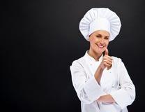 La donna del cuoco unico mostra okay cede firmando un documento il fondo scuro Fotografie Stock Libere da Diritti