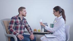 La donna del dietista di medico stringe le mani e gli aiuti all'uomo paziente fanno il piano di dieta per il benessere ed usando  archivi video