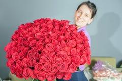 La donna del fiorista prepara un grande mazzo delle rose rosse Immagine Stock Libera da Diritti