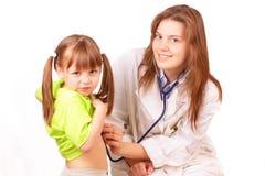 La donna del medico controlla la bambina immagine stock