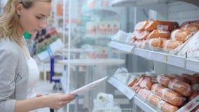 La donna del metraggio compra la salsiccia in supermercato video 4K video d archivio