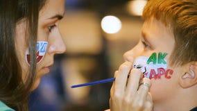 La donna del movimento lento disegna il trucco dell'acqua sulla guancia del bambino piccolo archivi video