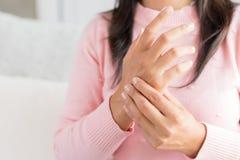 La donna del primo piano che si siede sul sofà tiene la sua lesione di mano del polso, feeli immagine stock