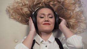 La donna del primo piano che si trova sul letto, mette lentamente le cuffie sopra le sue orecchie, reagisce alla musica, subtely  archivi video