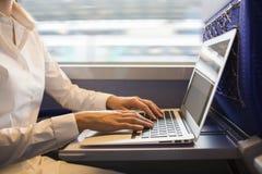 La donna del primo piano passa la battitura a macchina su una tastiera del computer portatile nel treno Fotografia Stock Libera da Diritti