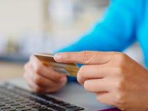 La donna del primo piano passa la tenuta della carta di credito e per mezzo del computer portatile Fotografia Stock Libera da Diritti