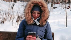 La donna del primo piano sta sedendosi sul banco e sul telefono cellulare di lettura rapida nel parco dell'inverno nella città du archivi video