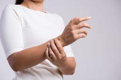 La donna del primo piano tiene la sua lesione di mano del polso, ritenente il dolore Sanit? e conept medico fotografia stock libera da diritti