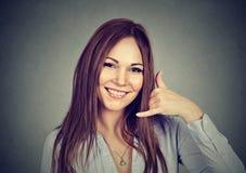 La donna del ritratto che rende a quadrante il mio segno di numero con la mano gradisce il telefono Immagine Stock