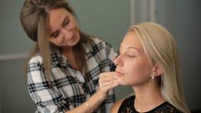 La donna del salone A di bellezza applica un fondamento biondo alla sua pelle video d archivio