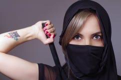 La donna del samurai si è vestita nel nero con il fronte di corrispondenza della copertura di velo, braccio della tenuta sulla pa Fotografie Stock