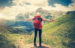 La donna del viaggiatore con le mani dello zaino ha sollevato l'alpinismo Fotografie Stock