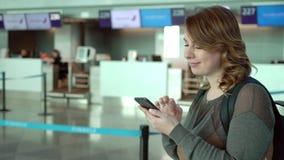 La donna del viaggiatore sta stando all'aeroporto prima della partenza Ragazza con lo zaino all'aeroporto video d archivio