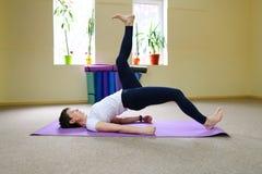 La donna dell'aspetto europeo si è impegnata nell'yoga nello studio di forma fisica Immagini Stock