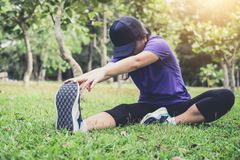 La donna dell'atleta che fa alcuni esercizi d'allungamento si scalda prima del funzionamento Fotografie Stock