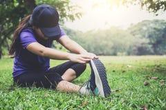La donna dell'atleta che fa alcuni esercizi d'allungamento si scalda prima del funzionamento Fotografia Stock Libera da Diritti