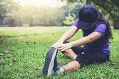 La donna dell'atleta che fa alcuni esercizi d'allungamento si scalda prima del funzionamento Fotografia Stock