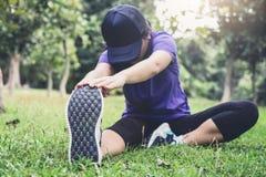 La donna dell'atleta che fa alcuni esercizi d'allungamento si scalda prima del funzionamento Immagini Stock Libere da Diritti