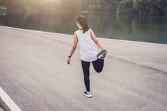 La donna dell'atleta che fa un certo allungamento esercita le gambe prima di runnin Immagini Stock